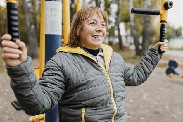 Vista lateral de uma mulher mais velha sorridente, malhando ao ar livre