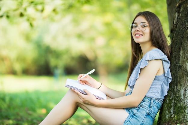 Vista lateral de uma mulher morena concentrada em óculos, sentada perto da árvore no parque e escrevendo algo no caderno
