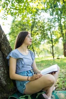 Vista lateral de uma mulher morena satisfeita em óculos, sentada na grama sob uma árvore e lendo um livro no parque