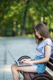 Vista lateral de uma mulher morena satisfeita em óculos, sentada no banco do parque e usando um computador portátil
