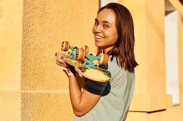 Vista lateral de uma mulher morena sorridente, vestindo uma camiseta casual azul, segurando o skate nas mãos, posando isolado na parede amarela ao ar livre, expressando emoções positivas.