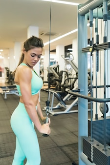 Vista lateral de uma mulher morena treinando os braços no ginásio