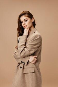 Vista lateral de uma mulher muito ruiva com um casaco em fundo bege