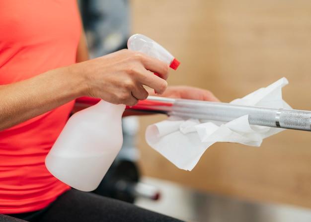 Vista lateral de uma mulher na academia desinfetando equipamentos