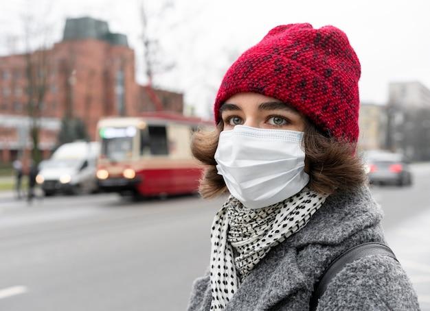 Vista lateral de uma mulher na cidade com máscara médica