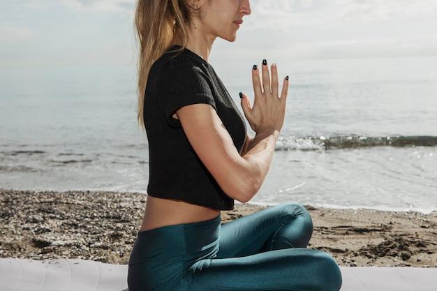 Vista lateral de uma mulher na praia em pose de ioga