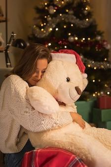 Vista lateral de uma mulher no natal abraçando seu ursinho de pelúcia com chapéu de papai noel
