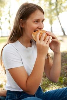 Vista lateral de uma mulher no parque comendo hambúrguer