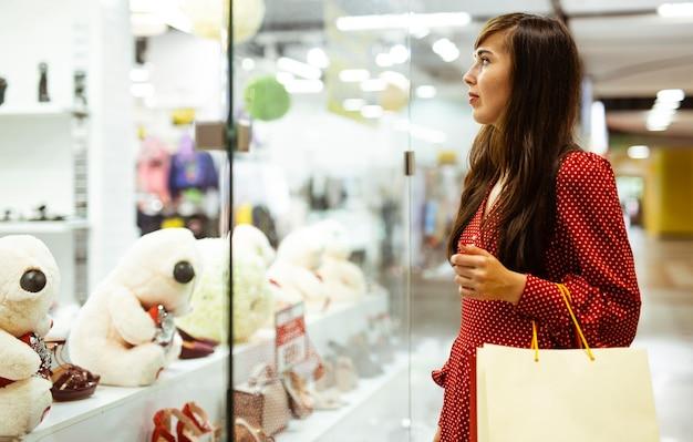 Vista lateral de uma mulher no shopping com sacolas de compras