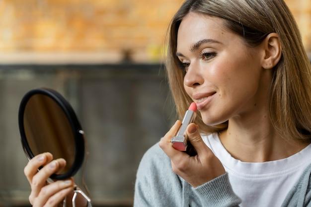 Vista lateral de uma mulher olhando no espelho enquanto passa batom