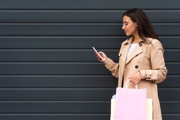 Vista lateral de uma mulher olhando para o smartphone enquanto segura sacolas de compras