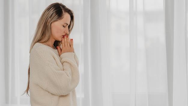 Vista lateral de uma mulher orando em casa com espaço de cópia