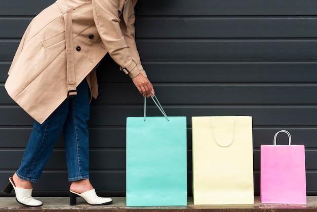 Vista lateral de uma mulher organizando sacolas de compras de tamanhos diferentes