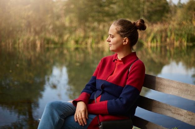 Vista lateral de uma mulher pensativa, sentada em um banco de madeira na margem do rio