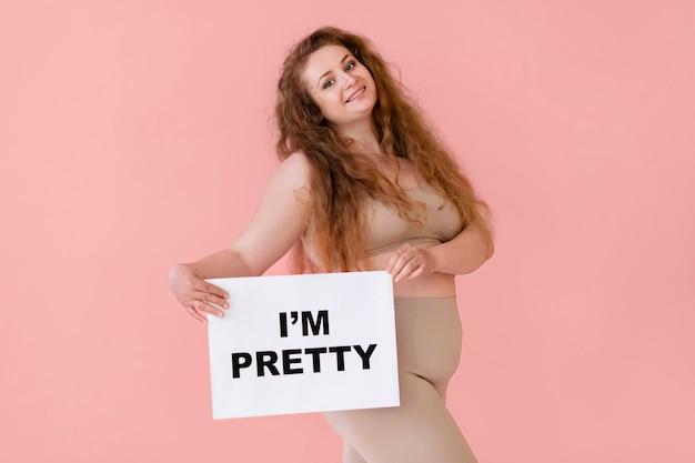 Vista lateral de uma mulher posando com um modelador de corpo e segurando um cartaz com a declaração de positividade corporal