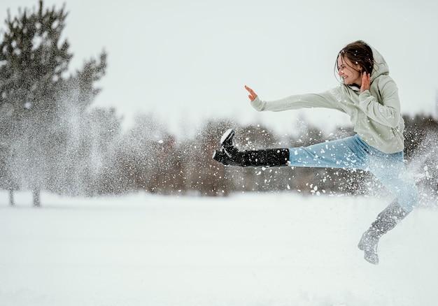 Vista lateral de uma mulher pulando ao ar livre no inverno