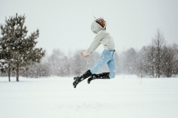Vista lateral de uma mulher pulando no ar ao ar livre no inverno