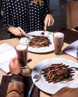 Vista lateral de uma mulher que come a sobremesa com bananas cobertas com chocolate e servido com cacau com marshmallow em vidro na mesa
