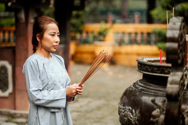 Vista lateral de uma mulher queimando incenso no templo
