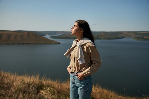 Vista lateral de uma mulher relaxada com os olhos fechados, em pé na colina verde com uma vista deslumbrante do rio dniester no fundo.