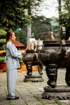Vista lateral de uma mulher religiosa queimando incenso no templo