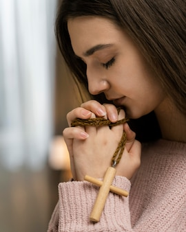 Vista lateral de uma mulher rezando enquanto segura uma cruz de madeira