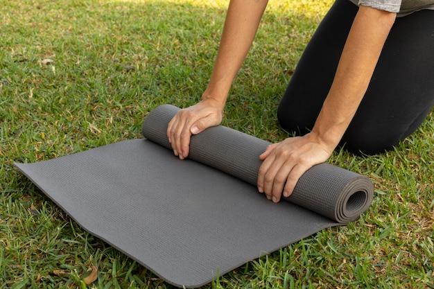 Vista lateral de uma mulher rolando o tapete de ioga na grama