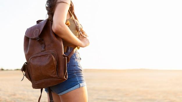 Vista lateral de uma mulher segurando a mochila enquanto ao ar livre com espaço de cópia