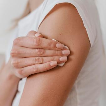 Vista lateral de uma mulher segurando o braço dela após tomar a vacina