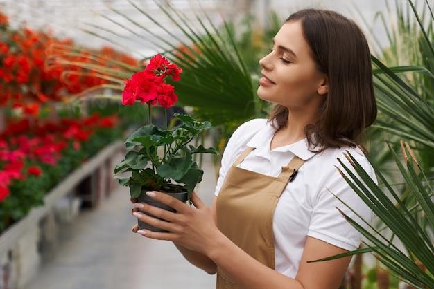 Vista lateral de uma mulher segurando o vaso com uma flor vermelha