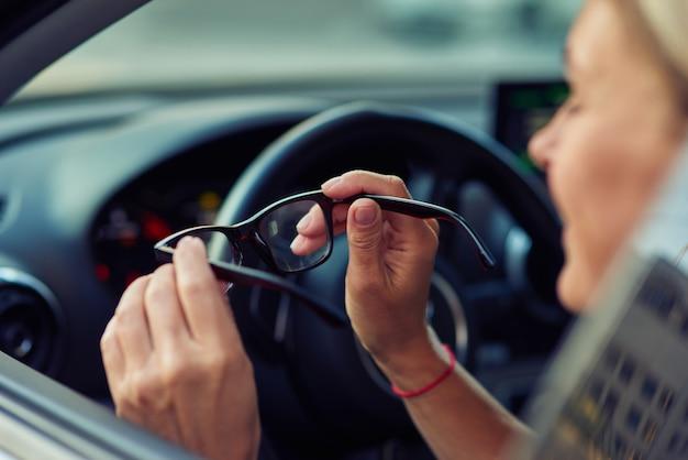 Vista lateral de uma mulher segurando óculos e sorrindo enquanto está sentada ao volante dela
