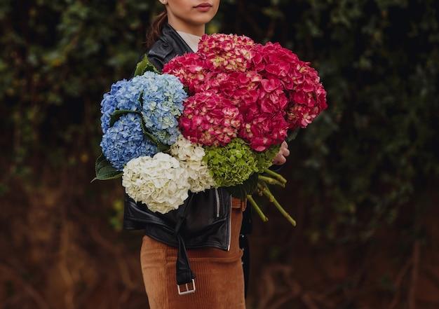 Vista lateral de uma mulher segurando um buquê de flores de hortênsia nas cores azuis e brancas cor de rosa
