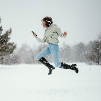 Vista lateral de uma mulher segurando um smartphone e pulando no ar ao ar livre enquanto usa fones de ouvido