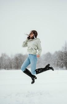 Vista lateral de uma mulher segurando um smartphone e pulando no ar ao ar livre