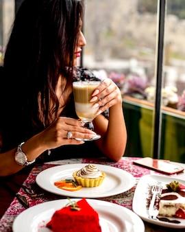 Vista lateral de uma mulher sentada à mesa com um copo de café com leite macchiato