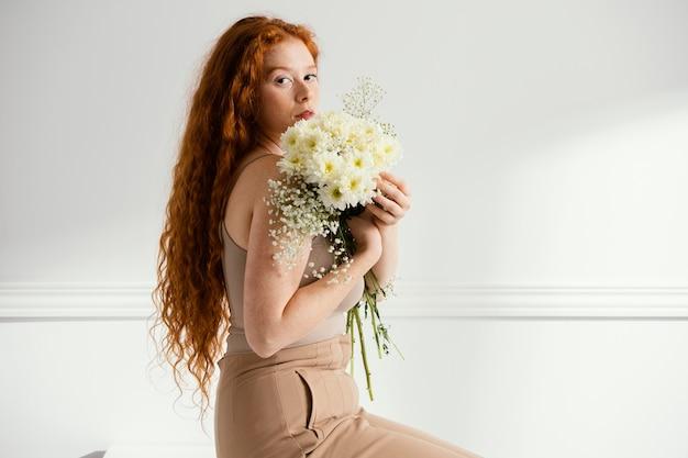 Vista lateral de uma mulher sentada na mesa e posando com flores da primavera
