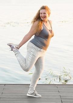 Vista lateral de uma mulher sorridente à beira do lago, estendendo-se