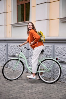 Vista lateral de uma mulher sorridente andando de bicicleta ao ar livre com um buquê de flores