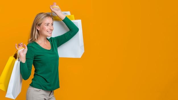 Vista lateral de uma mulher sorridente carregando muitas sacolas de compras