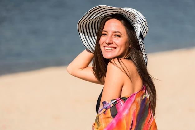 Vista lateral de uma mulher sorridente com chapéu posando na praia