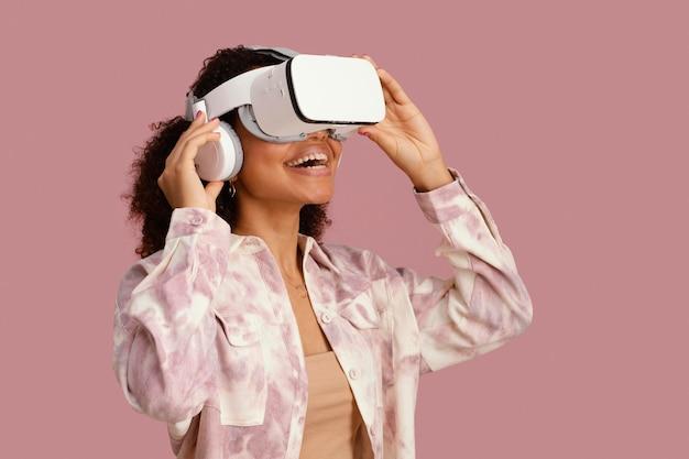 Vista lateral de uma mulher sorridente com fone de ouvido de realidade virtual