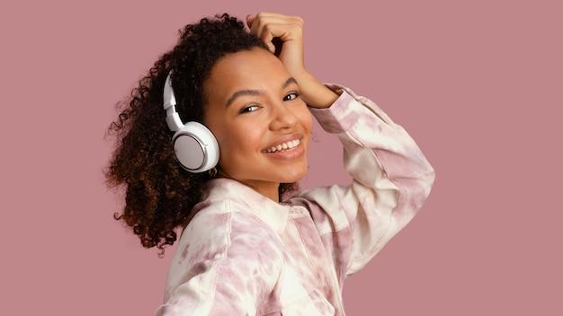 Vista lateral de uma mulher sorridente com fones de ouvido