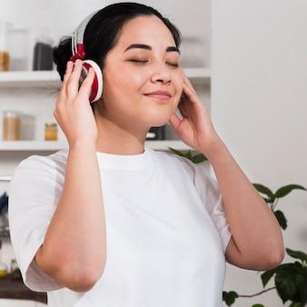 Vista lateral de uma mulher sorridente curtindo música em fones de ouvido