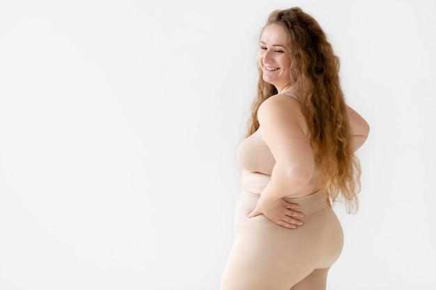 Vista lateral de uma mulher sorridente e confiante posando usando um modelador de corpo