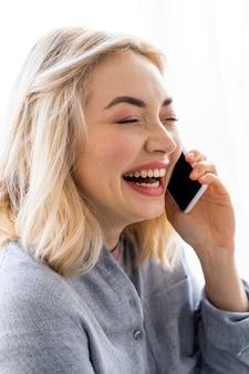 Vista lateral de uma mulher sorridente falando no smartphone