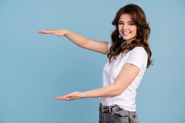 Vista lateral de uma mulher sorridente mostrando o tamanho com as mãos