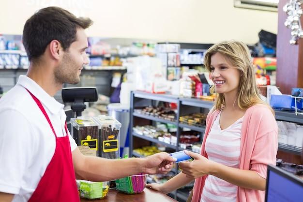 Vista lateral de uma mulher sorridente na caixa registradora com cartão de crédito