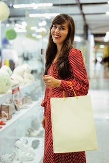 Vista lateral de uma mulher sorridente no shopping com sacolas de compras