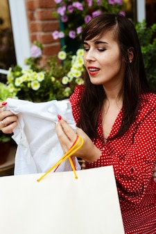 Vista lateral de uma mulher sorridente olhando para a promoção de roupas