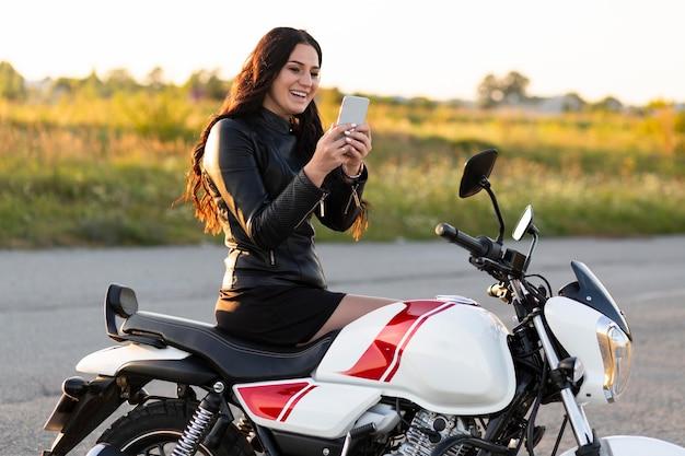 Vista lateral de uma mulher sorridente olhando para o smartphone enquanto está sentada em sua motocicleta